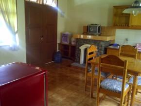Ruang tengah + TV, sofa, dispenser, kulkas, meja makan dan dapur bersih.